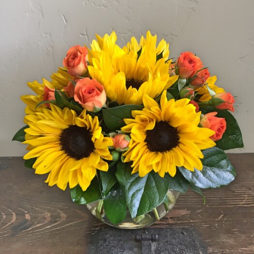 sunflowers, roses and greens in a small vase