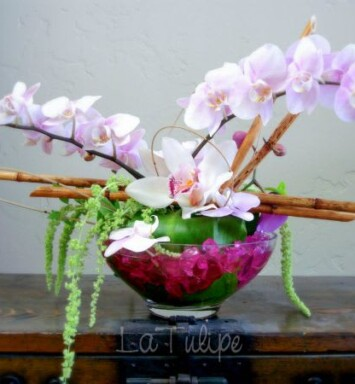 orchids in a bowl vase with bamboo