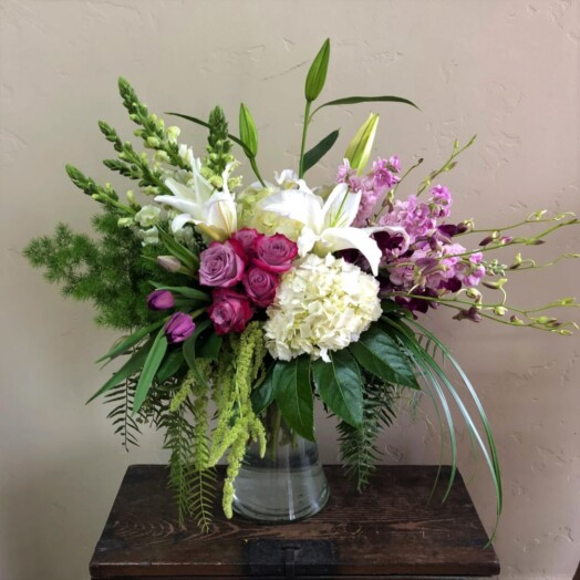 orchids, hydrangeas, roses in a large vase