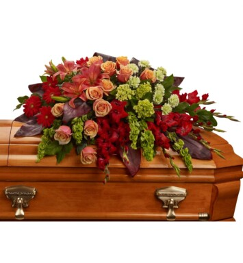 An overflowing of love and respect is joyfully expressed in this truly magnificent casket spray of orange roses and lilies and other brilliant blooms.
