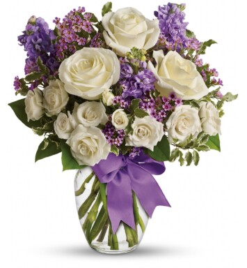 white roses with purple accents in glass vase