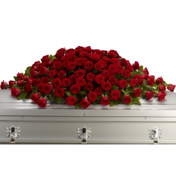 Red roses are arranged with rich green salal