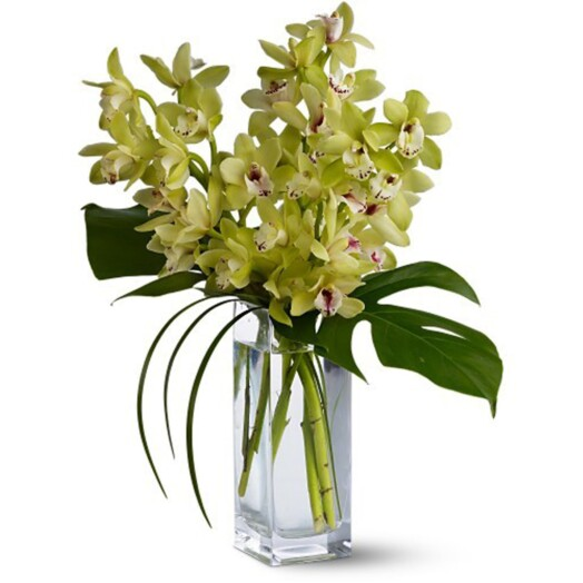 cymbidium orchids and lilies in a vase
