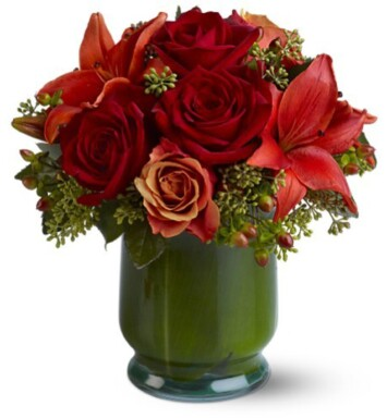 red roses and asiatic lilies in tea leaf lined vase