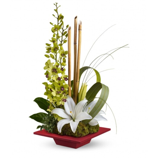 lilies and orchids in a flat vase