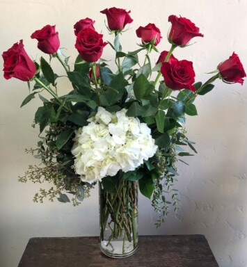 Red roses and hydrangea in tall vase with greens