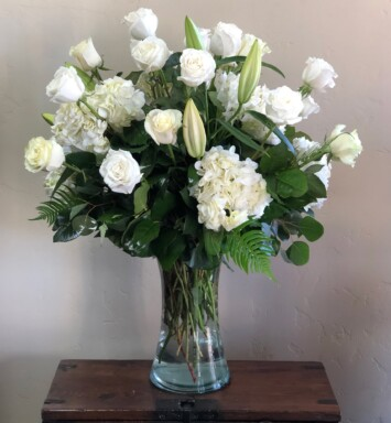 White flowers with greens in a vase